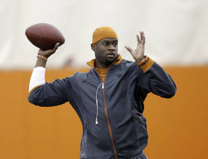 Photo - FILE - In this March 26, 2013 file photo, Former University of Texas and NFL quarterback Vince Young throws during Texas' Pro Day in Austin, Texas. The Green Bay Packers have signed free agent Young as a backup quarterback, Tuesday, Aug. 6, 2013. The 6-foot-5, 230-pound quarterback spent five seasons with the Tennessee Titans and one season with the Philadelphia Eagles. He was with the Buffalo Bills during the 2012 preseason.   (AP Photo/Eric Gay, File)
