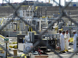 Photo - FILE - In this July 14, 2010 file photo, workers at the Hanford Nuclear Reservation stand near a tank farm where highly radioactive waste is stored underground near Richland, Wash. Few of the U.S. Department of Energy workers who are helping build the plant feel they can openly challenge decisions made by management, according to a report obtained Tuesday, June 24, 2014, by The Associated Press. (AP Photo/Shannon Dininny, File)