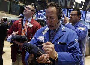 Photo - Trader Steven Kaplan, center, works on the floor of the New York Stock Exchange Friday, May 16, 2014. The stock market is little changed in early trading following sharp declines the previous day. (AP Photo/Richard Drew)
