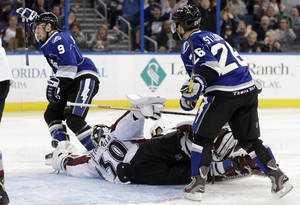 Photo - Tampa Bay Lightning center Tyler Johnson (9) celebrates after scoring past Colorado Avalanche goalie Sami Aittokallio (30), of Finland, during the second period of an NHL hockey game Saturday, Jan. 25, 2014, in Tampa, Fla. Looking on is Lightning's Martin St. Louis (26). (AP Photo/Chris O'Meara)