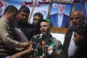 Photo - Ayman Sharawna, center, speaks during a rally calling for the release of Palestinian prisoners in Gaza City, Monday, March 25, 2013. Sharawna, a West Bank resident was deported to Gaza Strip last Sunday after a prolonged hunger strike in Israeli jail. (AP Photo/Hatem Moussa)