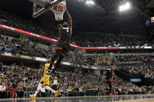 Photo - Miami Heat forward LeBron James (6) scores a break away dunk in front of Indiana Pacers forward Paul George (24) during the first half of an NBA basketball game in Indianapolis, Wednesday, March 26, 2014. (AP Photo/AJ Mast)