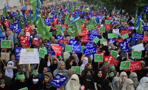 "Photo -   Supporters of Pakistani religious party Jamaat-e-Islami, hold up placards during a rally against a film insulting the Prophet Muhammad, in Lahore, Pakistan, Sunday, Oct. 7, 2012. Most placards read, "" Muhammad, may God pray on him and grant him peace."" (AP Photo/K.M. Chaudary)"
