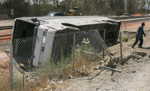 Photo - Salvage towing crews remove an overturned tour bus carrying gamblers to a casino on the 210 Southern California freeway injuring more than 50 people on board in Irwindale, Calif., on Thursday, Aug. 20, 2013. The bus went through a chain-link fence off the side of the road and ended up on its side down a dirt embankment between the freeway and railroad tracks. (AP Photo/Damian Dovarganes)
