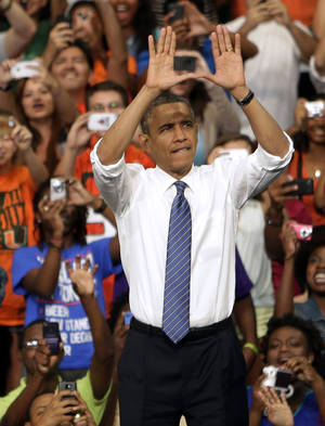 "Photo -   President Barack Obama does the sign of ""The U"" as he arrives a campaign event at the University of Miami, Thursday, Oct. 11, 2012, in Coral Gables, Fla. (AP Photo/Lynne Sladky)"