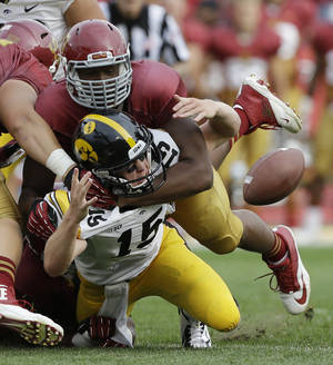 Photo - Iowa quarterback Jake Rudock (15) fumbles the ball as he is hit by Iowa State defensive lineman David Irving, top, during the first half of an NCAA college football game, Saturday, Sept. 14, 2013, in Ames, Iowa.  Iowa State recovered the fumble. (AP Photo/Charlie Neibergall)
