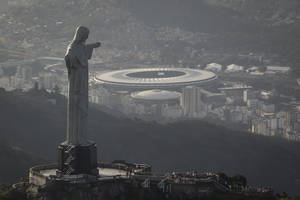 Photo - This aerial view shot through an airplane window shows the Maracana stadium behind the Christ the Redeemer statue in Rio de Janeiro, Brazil, Tuesday, May 13, 2014. As opening day for the World Cup approaches, people continue to stage protests, some about the billions of dollars spent on the World Cup at a time of social hardship, but soccer is still a unifying force. The international soccer tournament will be the first in the South American nation since 1950. (AP Photo/Felipe Dana)