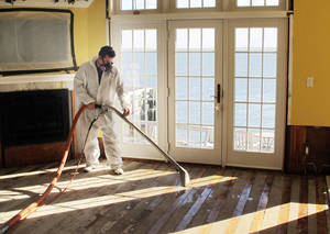 photo - In this Jan. 24, 2013 photo, Victor Pena of Flag Enterprises steam-cleans a floor in a home in Massapequa, N.Y. Homeowners in New York and New Jersey are struggling to combat outbreaks of mold from water-logged homes in the wake of Superstorm Sandy. (AP Photo/Frank Eltman, File)
