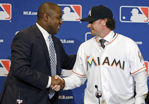 Photo - Michael Hill, left, president of baseball operations for the Miami Marlins shakes hands with Jarrod Saltalamacchia welcoming him to the team during a news conference at the MLB winter meetings in Lake Buena Vista, Fla., Monday, Dec. 9, 2013. Saltalamacchia signed a 3-year deal with the Marlins. (AP Photo/John Raoux)