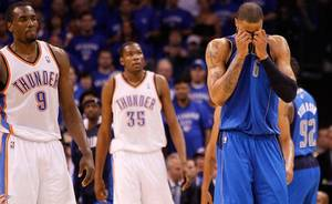 photo - Dallas Mavericks' Tyson Chandler, right, front, wipes his face as Oklahoma City Thunder's Serge Ibaka (9) of Republic of Congo and Kevin Durant (35) walk up the court in the second half of  Game 4 of the NBA Western Conference finals basketball series Monday, May 23, 2011, in Oklahoma City. (AP Photo/Eric Gay)