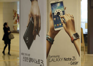 Photo - A woman uses her mobile phone near advertisements for Samsung Electronics' Galaxy Note 3 at a showroom of Samsung Electronics in Seoul, South Korea, Tuesday, Jan. 7, 2014. Samsung Electronics Co.'s fourth-quarter operating profit declined 6 percent over a year earlier, the company said Tuesday, underlining the challenges the world's largest smartphone maker faces as sales of mobile devices slow in advanced countries. (AP Photo/Lee Jin-man)