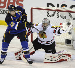 Photo - Chicago Blackhawks' goalie Corey Crawford, right, makes a glove-save against St. Louis Blues' David Backes (42) during the second period in Game 2 of a first-round NHL hockey playoff series on Saturday, April 19, 2014, in St. Louis. (AP Photo/Bill Boyce)