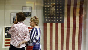"""Photo -  Edmond City Ccouncilwoman Elizabeth Waner, left, and Beth Kerr read information about the history of the American flag during """"Raise It Up!"""" at the Edmond Historical Society and Museum. Groups around the country gathered Saturday, in recognition of Flag Day, to sing the national anthem. PHOTO BY NATE BILLINGS, THE OKLAHOMAN  <strong>NATE BILLINGS - NATE BILLINGS</strong>"""
