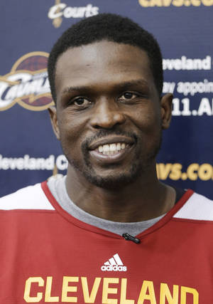 Photo - New Cleveland Cavaliers forward Luol Deng talks with reporters after his first practice with the NBA team at their practice facility in Independence, Ohio, Wednesday, Jan. 8, 2014. The Cavaliers traded Andrew Bynum and future draft choices for the two-time All-Star on Tuesday. (AP Photo/Mark Duncan)