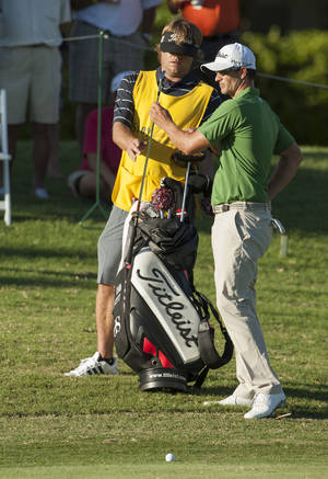Photo - Caddie Benji Weatherly, left, hands club to Adam Scott on the 18th fairway during the second round of the Sony Open golf tournament, Friday, Jan. 10, 2014, in Honolulu. (AP Photo/Marco Garcia)