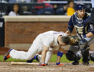 Photo - New York Mets David Wright (5) is assisted by Milwaukee Brewers catcher Jonathan Lucroy after Wright was hit in the head by a pitch in the third inning of a baseball game against the Milwaukee Brewers at Citi Field in New York, Thursday, Sept. 26, 2013. (AP Photo/Paul J. Bereswill)