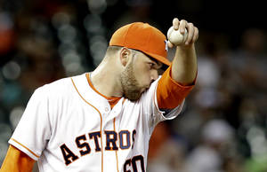 Photo - Houston Astros starting pitcher Dallas Keuchel wipes his face after giving up a single to Los Angeles Angels' Josh Hamilton in the third inning of a baseball game on Saturday, April 5, 2014, in Houston. (AP Photo/Pat Sullivan)