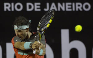 Photo - Rafael Nadal, of Spain, returns the ball to Pablo Andujar, of Spain, during a semifinal match at the Rio Open tennis tournament in Rio de Janeiro, Brazil, Saturday, Feb. 22, 2014. (AP Photo/Leo Correa)