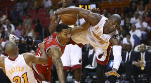 Photo - After blocking a shot by Chicago Bulls' Derrick Rose (1), Miami Heat's Dwyane Wade (3) falls to the court during the second half of a NBA basketball game in Miami, Tuesday, Oct. 29, 2013. The Heat won 107-95. (AP Photo/J Pat Carter)