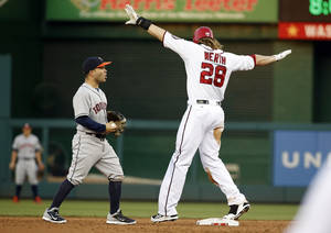 Photo - Washington Nationals' Jayson Werth, right, calls himself safe after Houston Astros second baseman Jose Altuve, left, missed the tag on Werth's steal of second base during the third inning of an interleague baseball game at Nationals Park Wednesday, June 18, 2014, in Washington. (AP Photo/Alex Brandon)