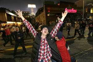 Photo - Boston Red Sox fans celebrate in the street near Fenway Park following Game 6 of baseball's World Series between the Red Sox and the St. Louis Cardinals, Wednesday, Oct. 30, 2013, in Boston. The Red Sox won 6-1 to win the series. (AP Photo/Steven Senne)