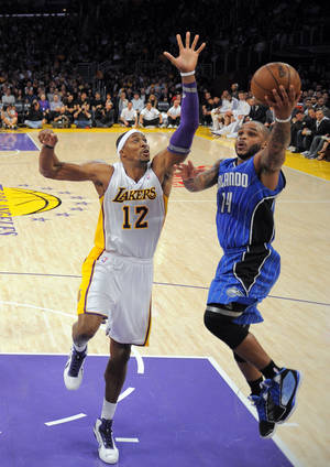 photo - Orlando Magic guard Jameer Nelson, right, puts up a shot as Los Angeles Lakers center Dwight Howard defends during the first half of their NBA basketball game, Sunday, Dec. 2, 2012, in Los Angeles. (AP Photo/Mark J. Terrill)