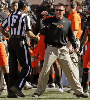 Photo - Oklahoma State head coach Mike Gundy argues a call with an official late in the second quarter during a college football game between the Oklahoma State University Cowboys (OSU) and the Kansas State University Wildcats (KSU) at Boone Pickens Stadium in Stillwater, Okla., Saturday, Oct. 5, 2013. Photo by Nate Billings, The Oklahoman