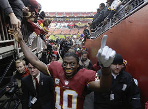 Photo -   Washington Redskins quarterback Robert Griffin III (10) greets fans as he leaves the field after an NFL football game against the Philadelphia Eagles in Landover, Md., Sunday, Nov. 18, 2012. The Redskins defeated the Eagles 31-6. (AP Photo/Patrick Semansky)