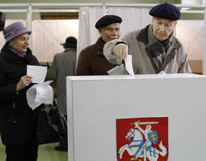Photo -   A Lithuanian voter casts his ballot at a polling station in Vilnius, Lithuania, Sunday, Oct. 14, 2012. Lithuanians are expected to deal a double-blow to the incumbent conservative government in national elections Sunday by handing a victory to opposition leftists and populists and saying 'no' to a new nuclear power plant that supporters claim would boost the country's energy independence. (AP Photo/Mindaugas Kulbis)