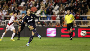 Photo -   Real Madrid's Cristiano Ronaldo from Portugal, centre, scores his goal during a Spanish La Liga soccer match against Rayo Vallecano at the Vallecas stadium in Madrid, Spain, Monday, Sept. 24, 2012. (AP Photo/Andres Kudacki)