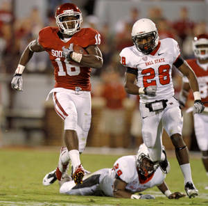 Photo - Oklahoma's Jaz Reynolds (16) runs past Ball State's Andre Dawson (28) after a cathc during the college football game between the University of Oklahoma Sooners (OU) and the Ball State Cardinals at Gaylord Family-Memorial Stadium on Saturday, Oct. 01, 2011, in Norman, Okla. Photo by Bryan Terry, The Oklahoman