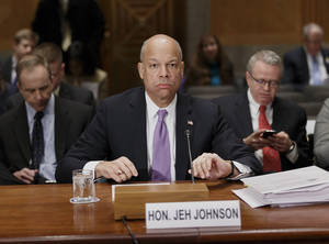 Photo - Homeland Security Secretary Jeh Johnson prepares to testify on Capitol Hill in Washington, Thursday, March 13, 2014, to outline President Barack Obama's FY2015 budget requests to the Senate Homeland Security and Governmental Affairs Committee.  (AP Photo/J. Scott Applewhite)