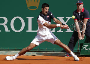 Photo - Novak Djokovic of Serbia, returns the ball to Pablo Carreno Busta of Spain during their third round match of the Monte Carlo Tennis Masters tournament in Monaco, Thursday, April 17, 2014. Djokovic won 6-0 6-1. (AP Photo/Michel Euler)