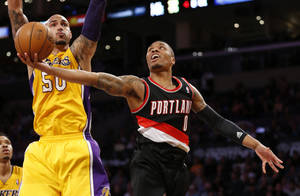 Photo - Portland Trail Blazers guard Damian Lillard, right, goes to the basket Los Angeles Lakers center Robert Sacre defends during the second half of an NBA basketball game in Los Angeles, Tuesday, April 1, 2014. (AP Photo/Danny Moloshok)