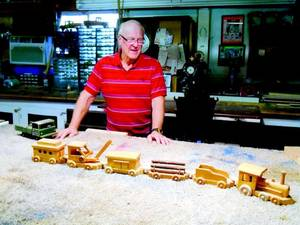 Photo - Ray Wise and a toy train he made from wood. (Muskogee Phoenix photo)