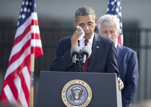 Photo - President Barack Obama, accompanied by Defense Secretary Chuck Hagel, wipes his face as he speaks during a 9/11 remembrance ceremony at the Pentagon, Wednesday, Sept. 11, 2013.    (AP Photo/Manuel Balce Ceneta)