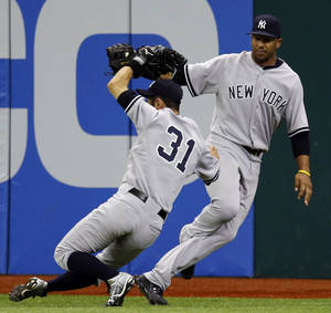 Photo -   New York Yankees center fielder Chris Dickerson, right, and right fielder Ichiro Suzuki, of Japan, collide chasing an eighth-inning fly out by Tampa Bay Rays' Ben Francisco during a baseball game, Monday, Sept. 3, 2012, in St. Petersburg, Fla. Disckerson eventually made the catch. The Rays won 4-3. (AP Photo/Chris O'Meara)