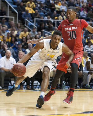 Photo - West Virginia's Terry Henderson, left, drives past Texas Tech's Jaye Crockett during the second half of an NCAA college basketball game Wednesday, Jan. 22, 2014, in Morgantown, W.Va. West Virginia won 87-81. (AP Photo/Andrew Ferguson)