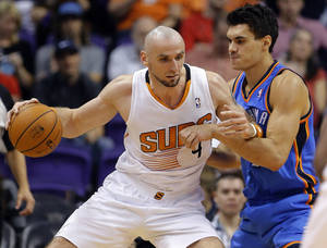 Photo - Phoenix Suns center Marcin Gortat, of Poland, backs down Oklahoma Thunder center Steven Adams, right, during the first half of an NBA preseason basketball game, Tuesday, Oct. 22, 2013, in Phoenix. (AP Photo/Matt York)