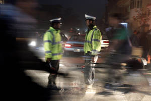 photo - Afghan traffic policemen stand near the scene where Afghanistan's Intelligence Chief Asadullah Khalid was wounded in an assassination attempt on him in Kabul, Afghanistan, Thursday, Dec. 6, 2012. Afghanistan's intelligence chief was wounded Thursday in an assassination attempt in the capital, Kabul, Afghan officials said. (AP Photo/Ahmad Jamshid)