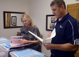 Photo - On Friday, Edmond North High School assistant principal Teresa Wilkerson and principal Jason Pittenger check to make sure all 135 staff handbooks are accounted for in preparation for the first day of Edmond Public Schools on Aug 17. <strong>Adam Kemp</strong>