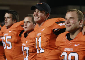 Photo -   Oklahoma State quarterback Wes Lunt (11) smiles as he sings the alma mater with his teammates following an 84-0 victory over Savannah State in an NCAA college football game in Stillwater, Okla., Saturday, Sept. 1, 2012. Standing with Lunt are defensive end Kaleb Cusak (65) and fullback Teddy Johnson (39). Number 47 is unidentified. Lunt threw for 129 yards while playing only four offensive series, the only tune-up the freshman will get before a road trip to Arizona next week. (AP Photo/Sue Ogrocki)