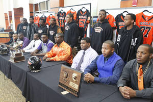 Photo - Other senior football players pose with the players signing to play college football during Wednesday's ceremony at Douglass High School. Photo by David McDaniel, The Oklahoman