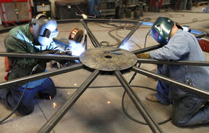 photo - Welders piece together a metal wheel at Pro-Formance Mfg. in Oklahoma City, OK, Tuesday, February 19, 2013. The company makes spooling trailers for various industries.  By Paul Hellstern, The Oklahoman