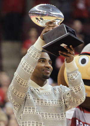Photo - Ohio State quarterback Braxton Miller raises the Silver Football, awarded by the Chicago Tribune to the best football player in the Big 10, during a timeout in an NCAA college basketball game between Ohio State and Northwestern on Wednesday, Feb. 19, 2014, in Columbus, Ohio. (AP Photo/Jay LaPrete)