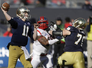 Photo - Notre Dame quarterback Tommy Rees  (11) throws a pass as lineman Mark Harrell (75) blocks Rutgers' Marcus Thompson (48) during the first half of the Pinstripe Bowl NCAA college football game Saturday, Dec. 28, 2013, at Yankee Stadium in New York. (AP Photo/Frank Franklin II)
