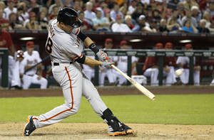 Photo - San Francisco Giants' Buster Posey connects for a 2-run home run against the Arizona Diamondbacks during the ninth inning of an opening day baseball game, Monday, March 31, 2014, in Phoenix. (AP Photo/Ross D. Franklin)