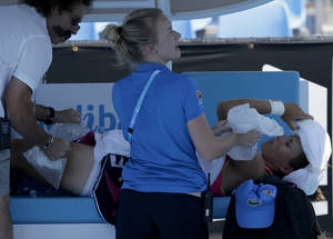 Photo - Varvara Lepchenko of the U.S. receives treatment for heat related illness during her second round match against Simona Halep of Romania during her second round match at the Australian Open tennis championship in Melbourne, Australia, Thursday, Jan. 16, 2014. (AP Photo/Aijaz Rahi)