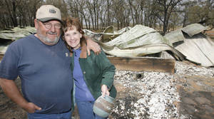 Photo - Jerry and Jammy England with the burned out  Cory's Cabin that was destroyed in Thursdays fires north of Lindsay, Friday, April 10, 2009. Cory's Cabin was belt to honor her son who died of cancer and was used as a church retreat and wedding were held there.   Photo By David McDaniel, The Oklahoman.