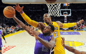 Photo -   Sacramento Kings point guard Tyreke Evans (13) shoots as Los Angeles Lakers center Dwight Howard (12) defends during the first half of their preseason NBA basketball game, Sunday, Oct. 21, 2012, in Los Angeles. (AP Photo/Mark J. Terrill)
